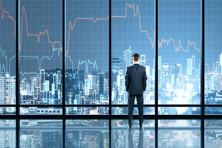 Businessman standing in office interior with glowing forex chart hologram. Trade and stats concept. Double exposure Standard-Bild