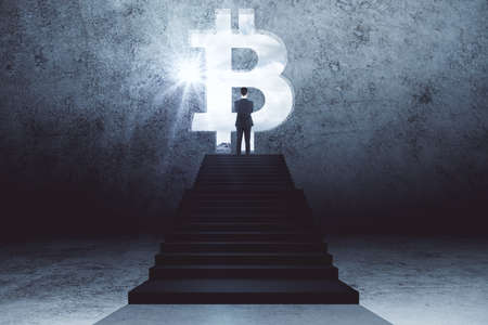 Young businessman standing on stairs and looking on glowing bitcoin sign. Business and cryptocurrency concept. Zdjęcie Seryjne