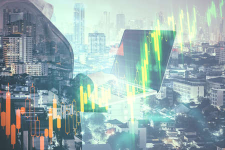 Businesswoman using laptop on blurry city background with forex chart. Trade and technology concept. Double exposure
