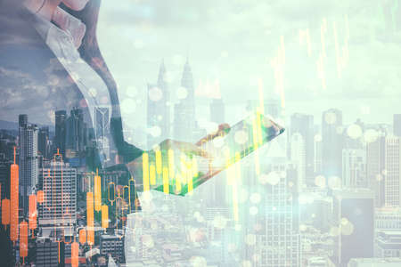 Businesswoman using tablet computer with stock chart on blurry city background. Trade and technology concept. Multiexposure Imagens