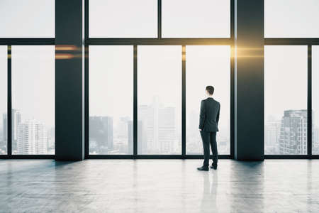Thoughtful businessmen in empty concrete hallway interior with bright daylight and city view. Leadership and success concept