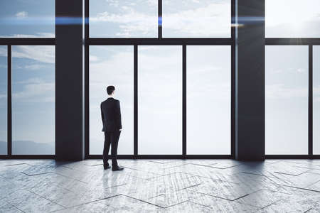 Young businessmen standing in empty concrete hallway interior. Leadership and success concept