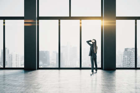 Businesswomen in empty hallway interior with bright daylight and city view. Leadership and success concept