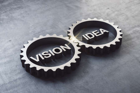 Two gears meshing together with text vision and idea on concrete table. Business and teamwork concept. 3D Rendering