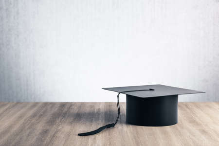 Black graduation cap on wooden table. Business and education concept. 3D Rendering