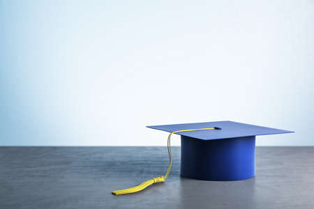 Blue graduation cap on wooden table. Business and education concept. 3D Rendering