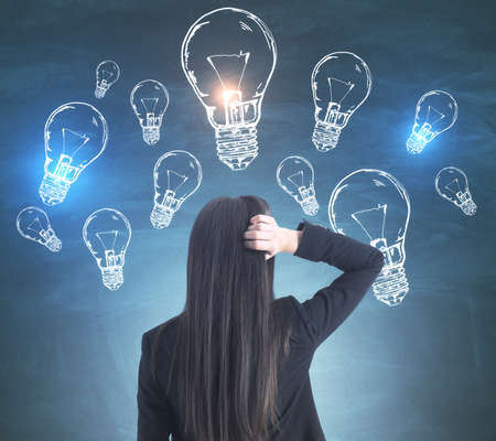Young european businesswoman looking on creative lightbulbs sketch on blue background. Brainstorm and innovation concept