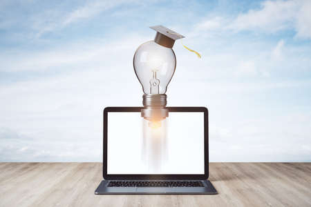 Rocket lamp in graduate cap and laptop on wooden table. Business and education concept. 3D Rendering Reklamní fotografie