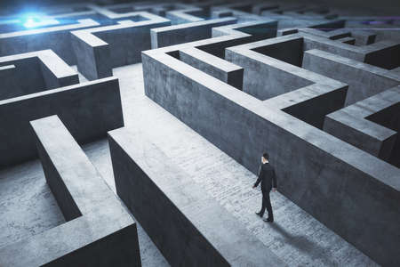 Businessman standing in middle of a concrete labyrinth. Business and challenge concept.