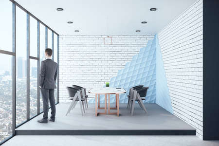 Businessman standing in loft conference interior with furniture, city view and blank gray wall. Occupation and worker concept. Reklamní fotografie