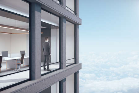 Businessman in suit stands in office in skyscraper and looking on blue sky view. Occupation and worker concept.