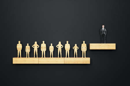 Wooden business people stand on shelf and businessman in suit stands on a step above. Business and management concept.