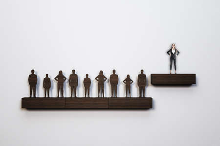 Wooden businesspeople stand on shelf and businesswoman stands on a step above. Business and management concept. Reklamní fotografie