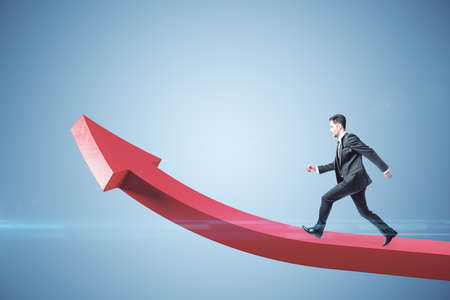 Businessman runing on red arrow on blue background. Growth and career development concept