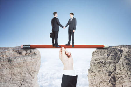 Businessman handshakin hand on red pencil on mountain on sky background. Leadership and success concept