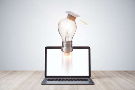 Rocket light bulb in graduate cap and laptop on wooden table. Business and education concept. 3D Rendering