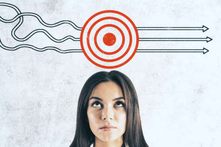 Businesswoman and drawing target with arrows on concrete wall. Leadership and way concept. Close up Stock Photo