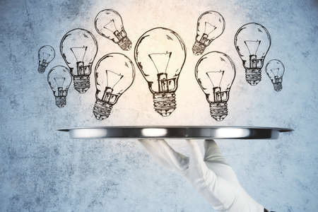 Hand holding tray many lightbulbs on concrete wall background. Start up and innovation concept.
