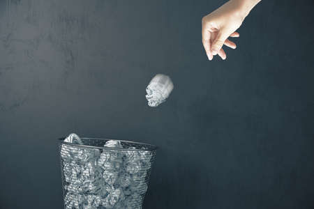 Hand trowing a paper into a wastebasket on gray concrete wall background. Business and paperwork concept.