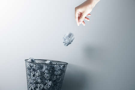 Hand trowing a paper into a wastebasket on gray background. Business and paperwork concept.