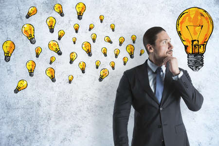Businessman with drawing yellow lightbulbs sketch on concrete wall. Success and startup concept.