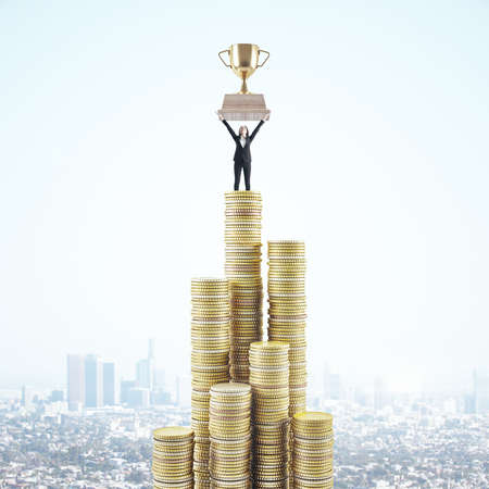 Businesswoman standing on stack golden coins and holding winner cup on panoramic city background. Winner and leadership concept.