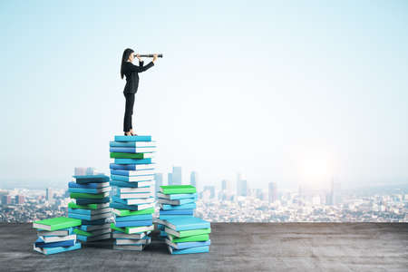 Young businesswoman with binocular standing on color books on city background. Growth, knowledge and vision concept Stok Fotoğraf