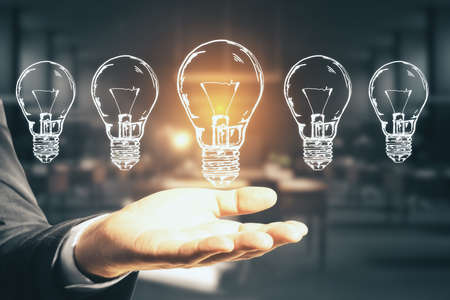 Businessman hand holding five drawing abstract light bulbs. Success and startup concept. Close up