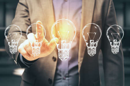 Businessman hand pushing five drawing light bulbs. Success and startup concept. Close up