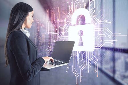 Woman working with laptop on lock symbol hologram with microcircuit background, double exposure, digital security concept Banco de Imagens