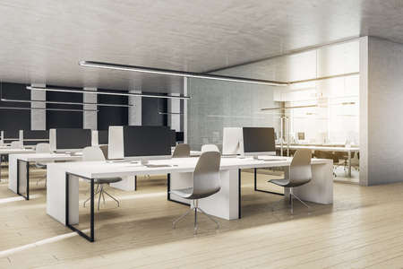 Coworking office in a loft style interior with computers and office chairs. Workplace and company concept. 3D Rendering