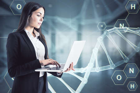 Woman working with laptop on a virtual DNA hologram background Imagens