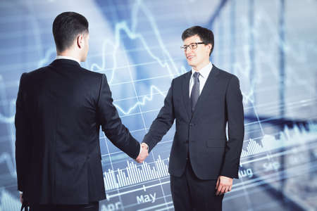 Two businessmen in suits shaking hands on the background of financial chart in office, deal and partnership concept