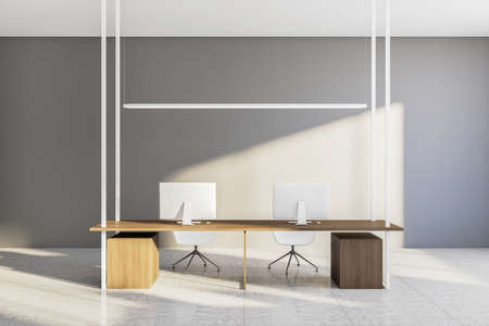 Contemporary workplace with two computers on long wooden table and blank concrete wall. Workplace and corporate concept. Mock up. 3D Rendering