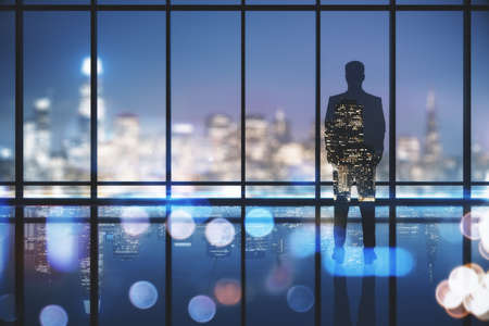 Businessman looking out of window in clean empty office interior with illuminated panoramic city view. Research concept.