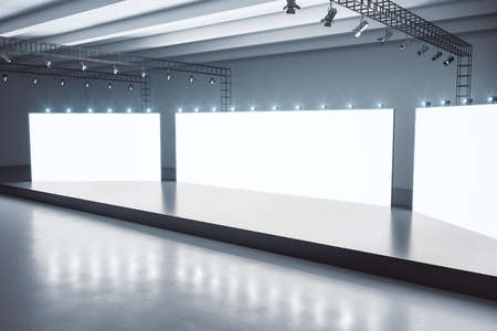 Black glosy stage in the center of empty spacious hall with white screens with copyspace and dark concrete floor. Mock up, 3D rendering