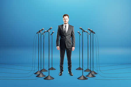 Business speaker on-stage concept with businessman and floor stand microphones around on blue background