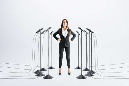 Business speaker concept with confident businesswoman and floor stand microphones around on light background