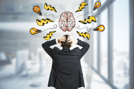 Idea and brainstorm concept with businessman in in front of handwritten sign of human brain, yellow lightning strike symbols and light bulbs