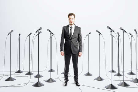 Public speaking skill concept with businessman among floor stand microphones on light background