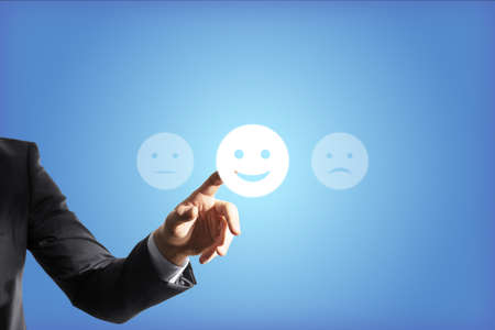 Businessman hand touches the good emoticon, blue background, feedback concept