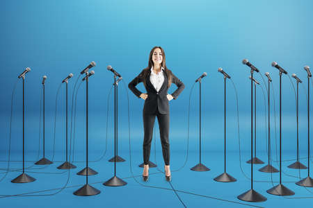 Business conference concept with businesswoman speaker among floor stand microphones on blue background