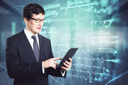 Online education and studying concept with student working on digital tablet on digital board with mathematical formulas background Standard-Bild