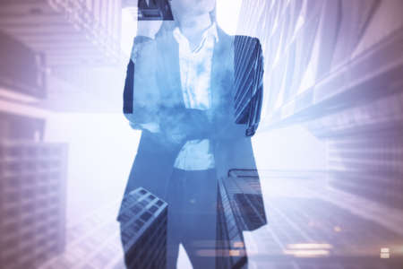 Businesswoman standing thinking with skyscrapers in the background, decision and entrepreneurship concept, double exposure