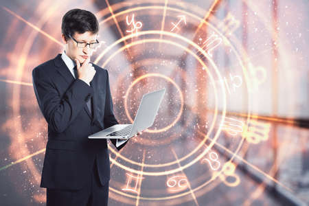 Businessman holding a laptop and thinking in an office corridor with a circle with zodiac signs, prediction and astrology concept