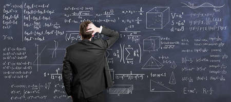Education concept with back view on pensive man in black suit looking at chalkboard painted with mathematical formulas Banque d'images