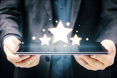 Businessman hands holding tablet with glowing stars on blue background. Customer feedback and online ranking concept