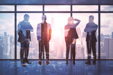 Team work and business partnership concept with businessmen silhouettes on high floor skyscraper looking through transparent glass wall on megapolis city at sunset