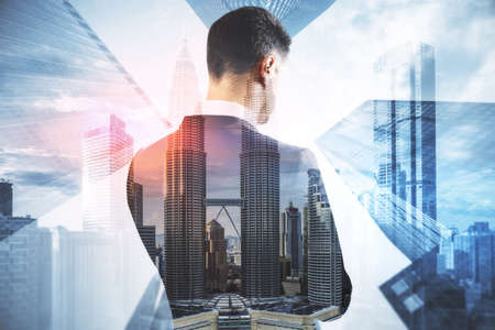 Back view of young businessperson standing on abstract city background with mock up place. Success and tomorrow concept. Double exposure