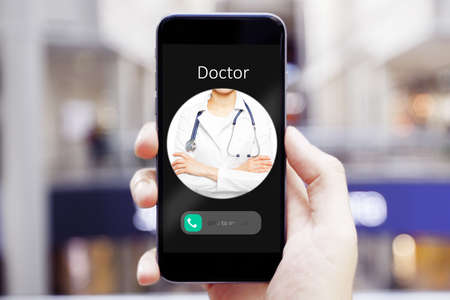 Hand holding cellphone with incoming call from doctor 免版税图像